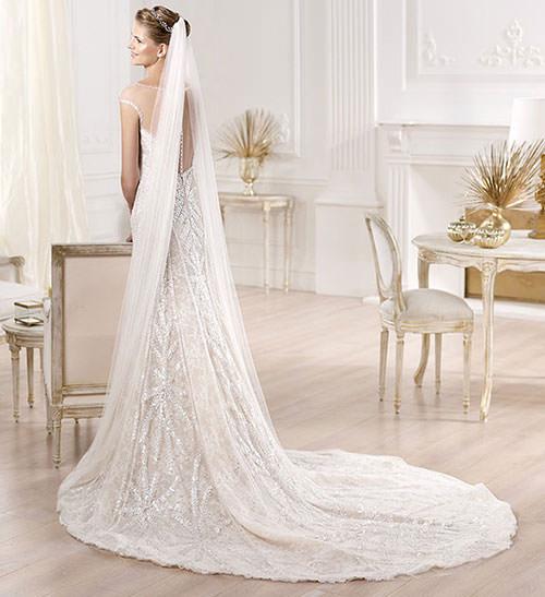 Parte traseira do vestido de noiva com pedrarias super elegantes e com véu.Fonte da imagem: Reprodução/Mod Wedding